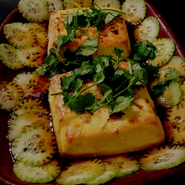 Baked egg tofu. Garnished with cilantro and cukes, flavored with garlic, lime leaf, soy and sesam...