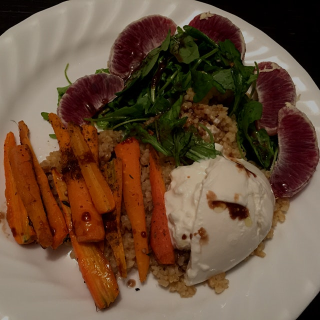 Roasted carrots with burrata, arugula and blood oranges over bulgar.