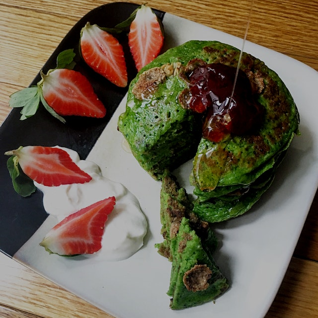 Spinach and matcha green pancakes topped with Crofter's raspberry jam and Wholefoods organic hone...