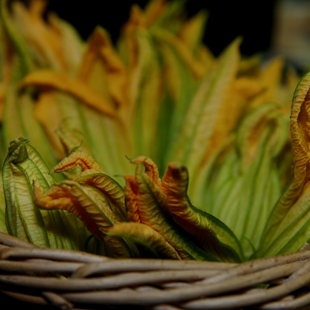 You'll see some zucchini blossoms at the farmers market. Quick-fry them and stuff 'em with ricott...