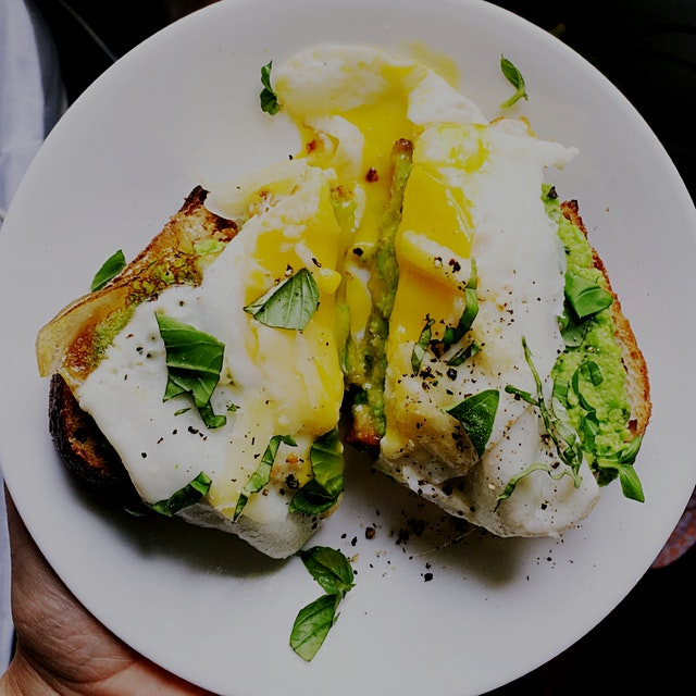 Smashed peas ( peas, olive oil, mint , basil) with a fried egg, white cheddar,  and basil on sour...