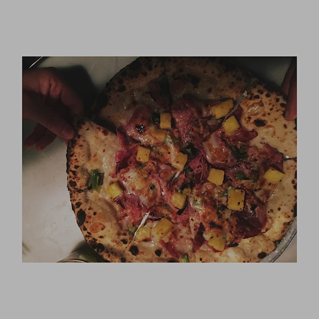 Wood fired pizza with speck pineapple and roasted scallion.