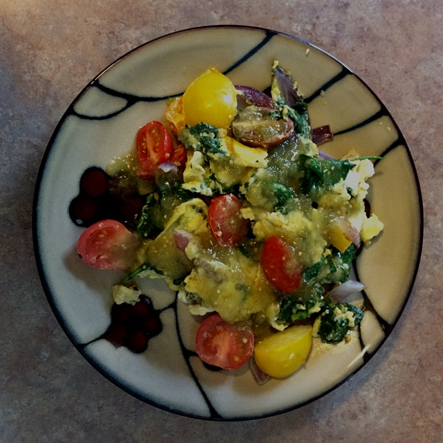 Sautéed red onion, spinach, heirloom tomatoes, and garlic with farm fresh eggs. Topped with some ...