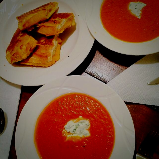 My tomato soup with a dollop of herbed goat cheese crème fraîche and grilled cheddar cheese toast...