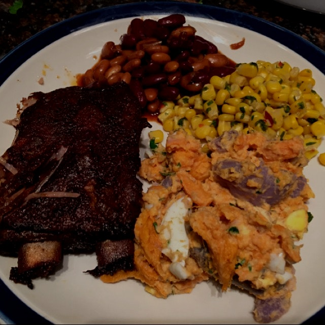 Slow cooked ribs, slow cooker bbq beans, blue and sweet potato salad and corn with chills and cil...