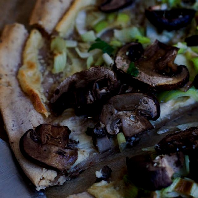 Flatbread pizza made with cassava flour, cashew cheese, leeks and mushrooms. Gluten-free, vegan a...