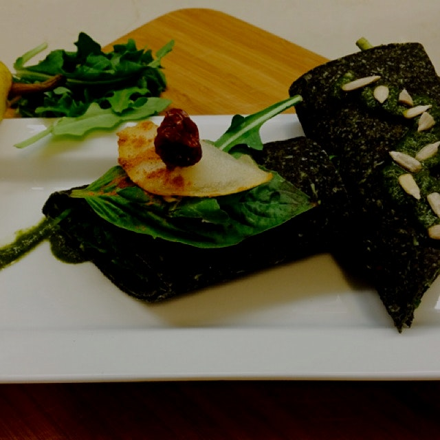 Raw sprouted spirulina wrap with pesto rubbed greens, pear and cashew cream cheese