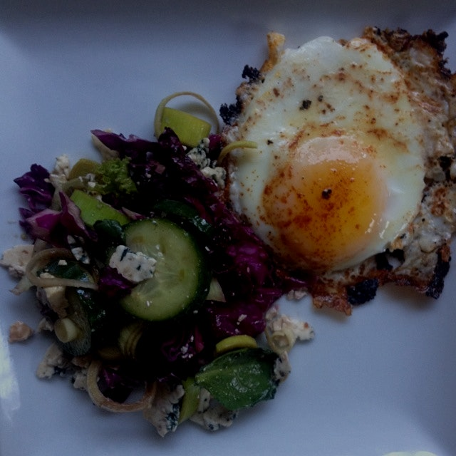 Fried egg with a red cabbage and cucumber salad.