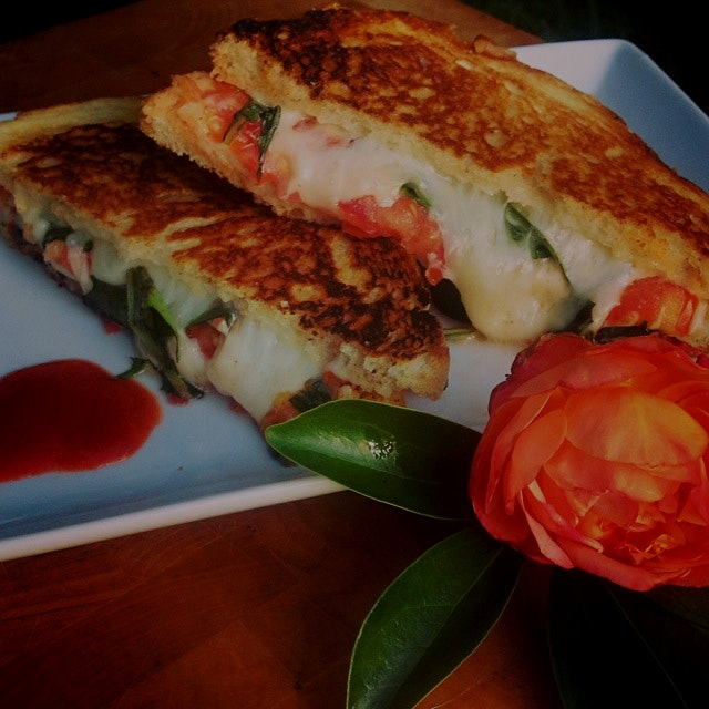 Manchego and Swiss Grilled cheese sandwich with shaved onion, sliced tomato, and dandelion greens:)