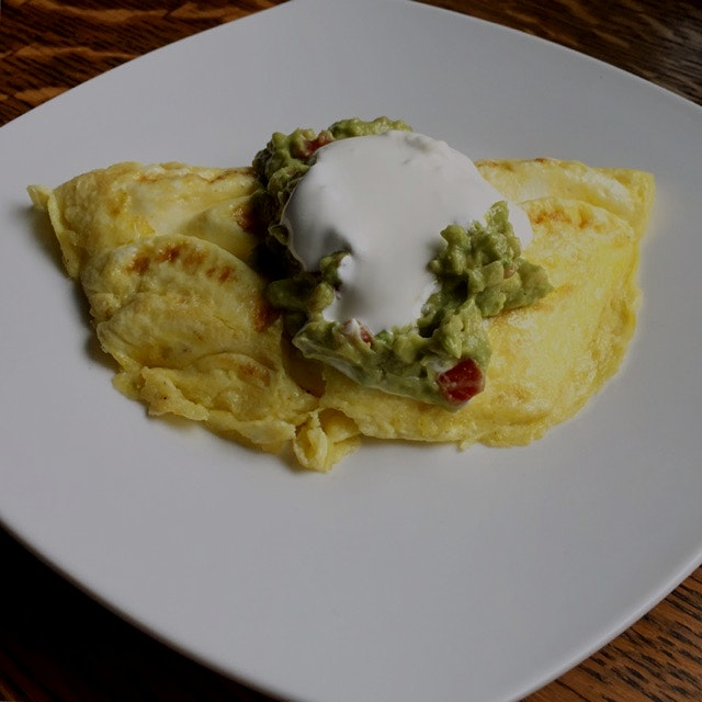 A post Cinco De Mayo breakfast consisting of a goat cheese omelet topped with fresh guacamole and...