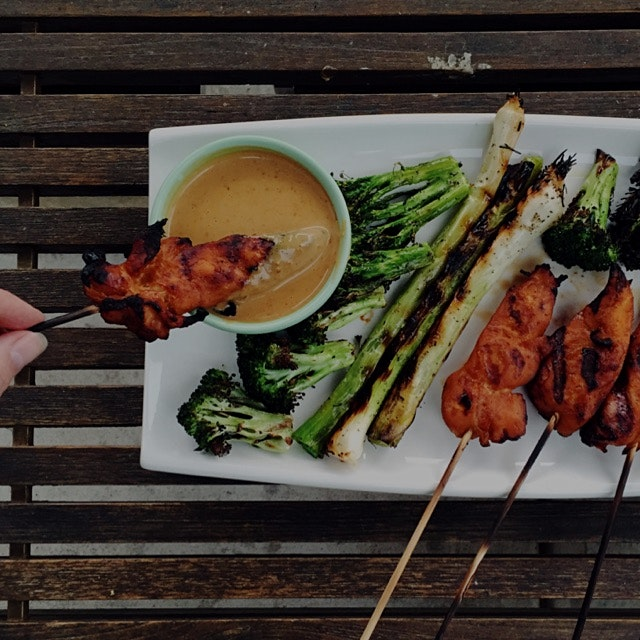 Dinner al fresco. Red curry + coconut chicken skewers, grilled local leeks + broccoli, and peanut...