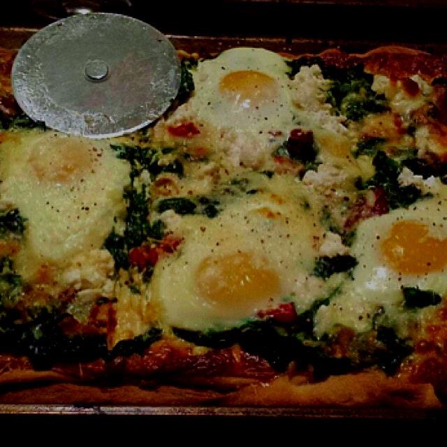 Pizza night!!  Garlic and cheese pie topped with spinach, eggs, and jarred chiles we bought in Pu...