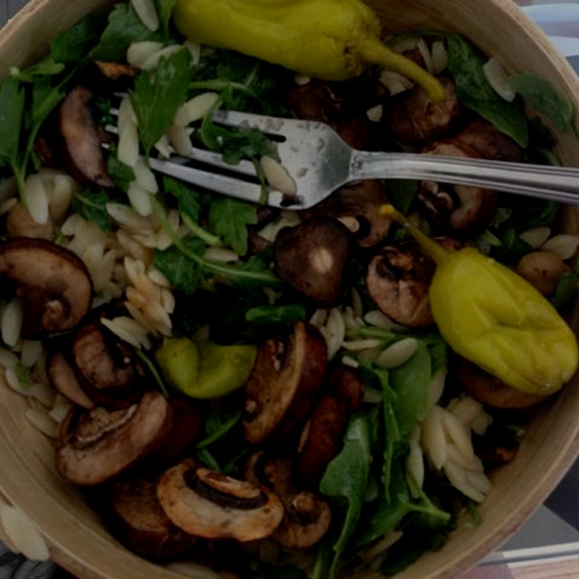 Orzo salad with kalamata olives, peperoncino, parsley, chickpeas, and mushrooms. Dressed with sim...