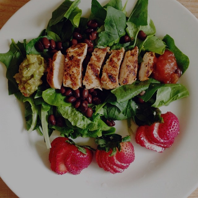 Pan grilled chicken, black beans, guacamole, and salsa on spinach and lettuce from the vegetable ...