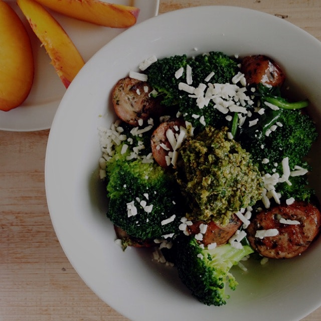 Chicken sausage, steamed broccoli, and sautéed spinach bowl with feta and topped with a big dollo...