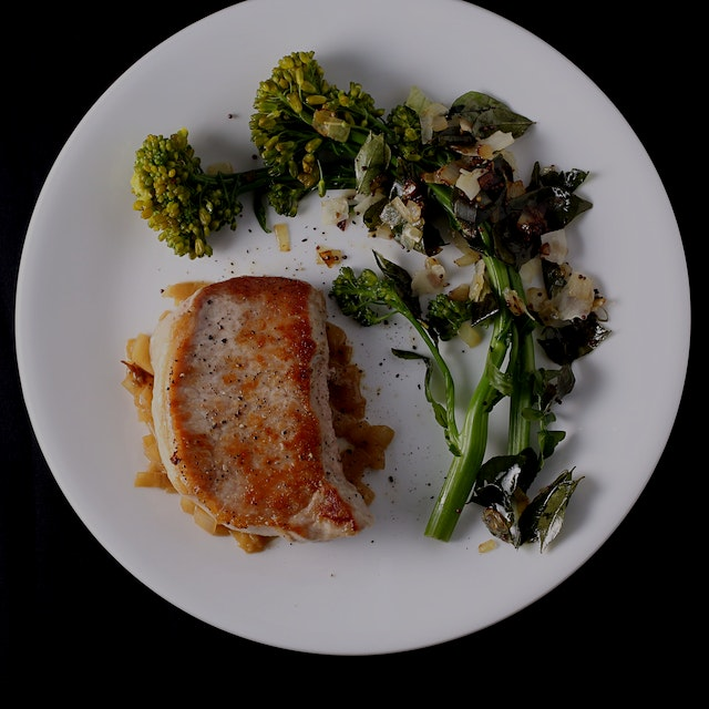 Pork chops and broccoli raab with coconut flakes and shallots.