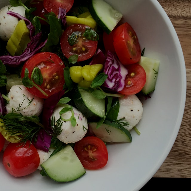 summer salad with cucumbers tomatoes mozzarella honey and herbs