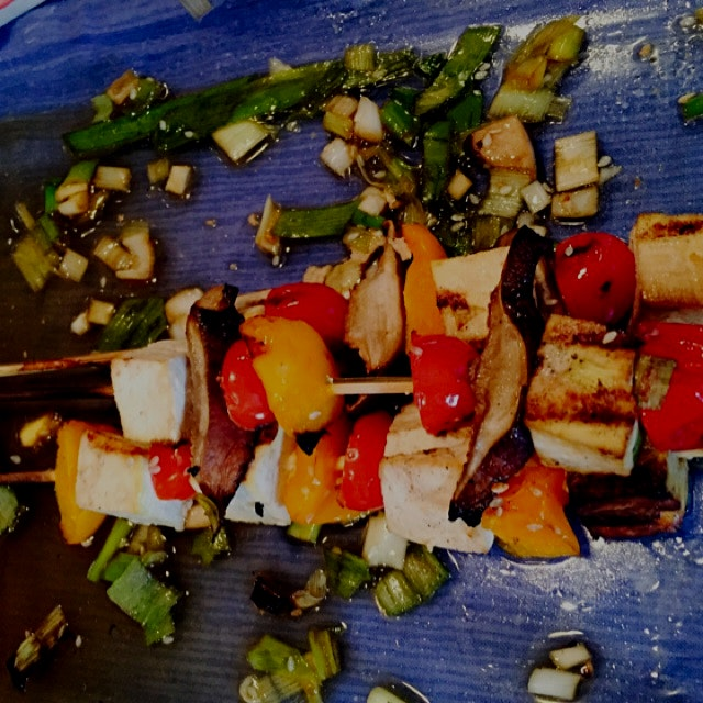 Tofu skewers marinated in a ginger soy honey sesame glaze with scallions and sesame seeds.
