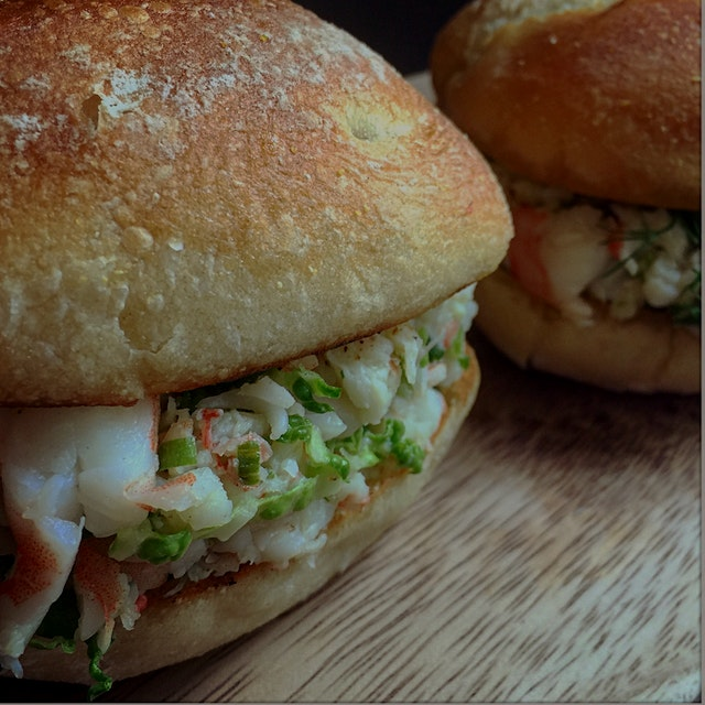Shrimp rolls with chives fennel cabbage and butter on a warm sourdough bread roll