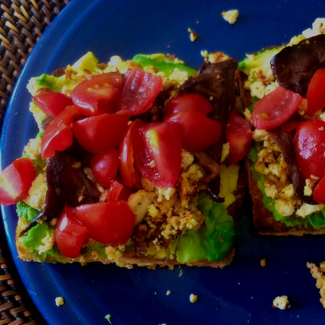 Amped up vegan avocado toast with tofu scramble and smoky eggplant.