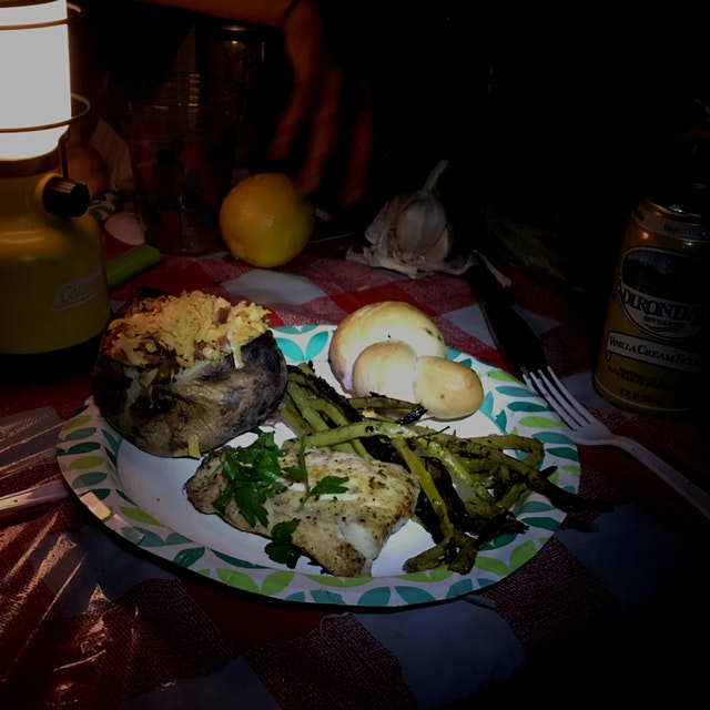 Rhode Island camping cuisine: fresh-caught local striper with smoky fire-roasted asparagus, loade...