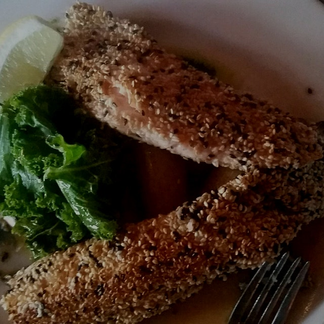 Baked trout coated with sesame seeds served with sautéed kale and fingerling potatoes- tasted lov...